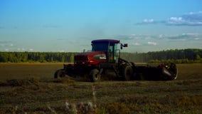 Movimientos modernos del rastrillo del tractor en las franjas de la paja de las formas del campo almacen de metraje de vídeo