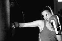 Movimientos practicantes del boxeador de sexo femenino en el saco de arena imágenes de archivo libres de regalías