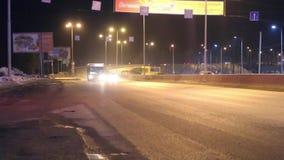 Moving автомобили, шины и знамена рекламы с освещением на ноче видеоматериал