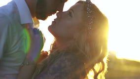 Moving взгляд нежно обнимая и целуя молодой пары во время захода солнца Портрет Конца-вверх сток-видео