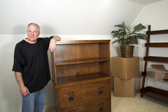 Moving In. Man standing next to bare furniture and moving boxes in his new home Stock Photography
