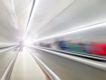 Moving on abstract escalator up the tunnel with people Royalty Free Stock Photo