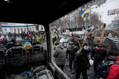 Moving activists walk past the barricades with police squads behind on the occupying snow street during anti-government protest. KYIV, UKRAINE: Moving activists stock photos