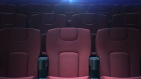 Moving along empty cinema chairs with the back light seamless. Looped 3d animation of rows of red seats in cinema hall