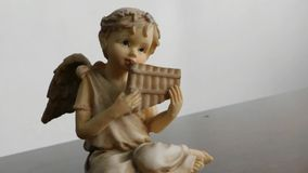 Moving away from a figurine of an angel playing a musical instrument. Video showing an angel figurine playing a musical instrument stock footage