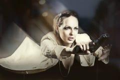 Moving beautiful woman. Holding gun on night street Stock Photo