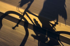 Moving Bicycle Shadow. The shadow of a moving bicyclist stands out against a blur of pavement Royalty Free Stock Photography