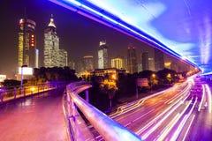 Moving bil med blurlampa till och med stad på natten Royaltyfri Bild