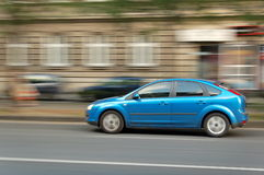Moving blue car. Blue fast moving car with blurred background due to following the car in Budapest at main street stock photography