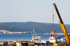 Moving of boat with crane in a port Royalty Free Stock Photography