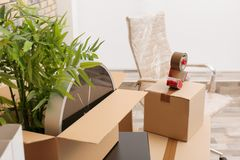 Moving box with office stuff on table indoors. Closeup Stock Image
