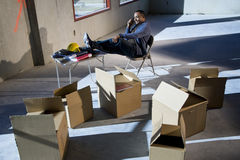 Moving boxes. African American man surrounded by boxes in empty unfinished office space Stock Photography