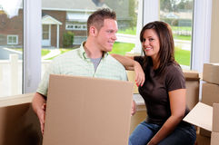 Moving Boxes. Young Couple Moving Into Their New Home Surrounded By Cardboard Boxes Stock Images