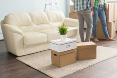 Moving boxes on carpet infront of young couple and sofa stock photography