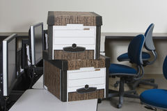 Moving Boxes And Chairs In Office. View of moving boxes by chairs on office desk royalty free stock images
