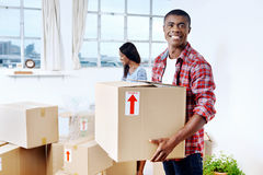 Moving boxes couple. Young black african couple moving boxes into new home together making a successful life Royalty Free Stock Photo