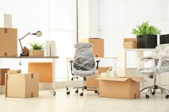 Moving boxes and furniture. In new office stock images