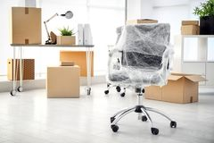 Moving boxes and furniture. In new office stock photos