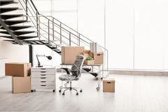 Moving boxes and furniture. In new office Royalty Free Stock Photos