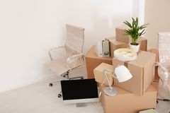 Moving boxes and furniture in new office. Space for text royalty free stock photography