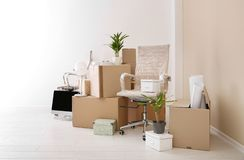 Moving boxes and furniture in new office. Space for text stock images