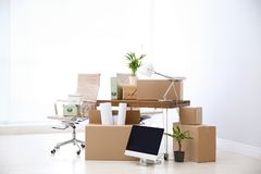 Moving boxes and furniture in new office. Space for text stock image