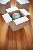 Moving Boxes Globe. Moving boxes with the open box containing a globe on a wood floor background royalty free stock photo