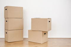 Moving Boxes in a Room. Two stacks of moving boxes on the floor of an empty room with a white wall Stock Image
