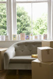 Moving Boxes By Sofa With Cards On Windowsill Stock Photography