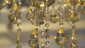 Moving of a bright crystal chandelier on a dark background. Slowly stock video footage