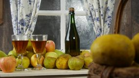 Moving camera slider showing bottle and glasses of cider with apples. In rustic house. Moving camera slider showing bottle and glasses of cider with apples. In stock video footage