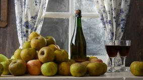 Moving camera slider showing bottle and glasses of cider with apples. In rustic house. Moving camera slider showing bottle and glasses of cider with apples. In stock footage