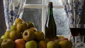 Moving camera slider showing bottle and glasses of cider with apples. In rustic house. Moving camera slider showing bottle and glasses of cider with apples. In stock video