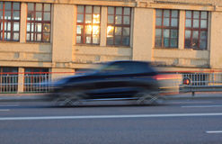 Moving car with motion blur effect. Motion blurred car on the street in the daytime royalty free stock photo