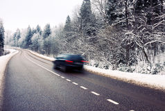 Moving car on the road in winter. Lonely car in motion blur on the road in winter landscape royalty free stock image