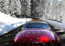 Moving car on snowy winter road. Red car on a forest road in winter, heavy snowfall royalty free stock photo