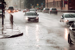 Moving car sprays puddle when heavy rain drops on concrete Stock Photography