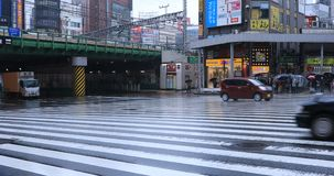 Moving cars at the crossing in Shinjuku Tokyo rainy day stock footage