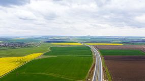 Moving cars on a fast road between rape fields royalty free stock photos