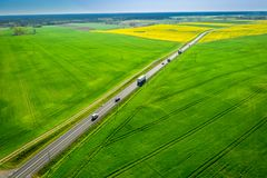 Moving cars on a fast road between rape fields royalty free stock images