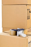 Moving carton boxes stack with tape roller Royalty Free Stock Photography