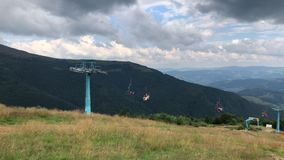Moving chair lift with people against the backdrop of the mountains. stock video footage
