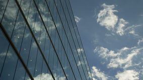 Moving clouds reflect onto office windows stock video footage