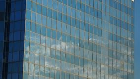 Moving clouds reflected in a glass wall of the building stock video