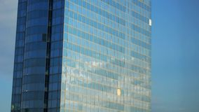 Moving clouds reflected in the glass wall of a skyscraper stock video footage