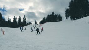 Moving clouds at a ski resort. People skiing downhill with moving clouds in the background stock video footage