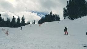 Moving clouds at a ski resort. People skiing downhill with moving clouds in the background stock footage
