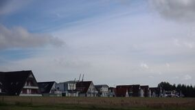 Moving clouds time-lapse at North Sea coast Germany with holiday apartments and houses
