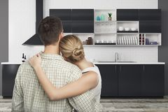 Moving concept. Back view of young european couple looking at modern kitchen interior. Moving concept. 3D Rendering Stock Image