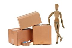 Articulated Wooden Mannequin Beside Cardboard Boxes and a Roll of Adhesive on White Background. Moving concept with wooden hinged dummy beside cardboard boxes stock photography